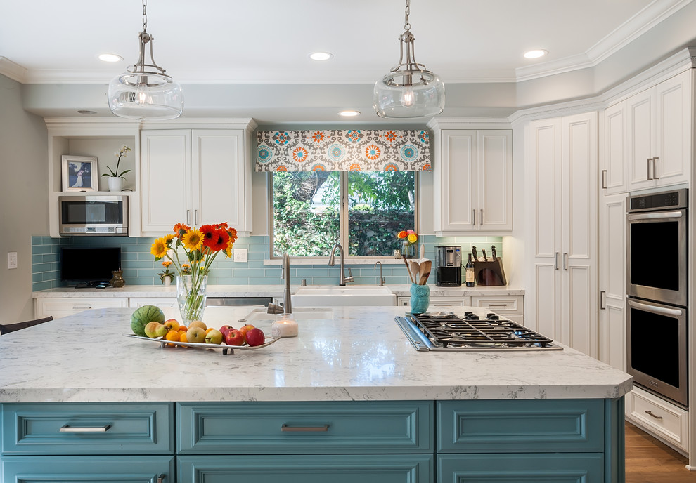 Example of a large beach style l-shaped light wood floor and multicolored floor open concept kitchen design in Los Angeles with a farmhouse sink, beaded inset cabinets, white cabinets, quartz countertops, blue backsplash, glass tile backsplash, stainless steel appliances and an island