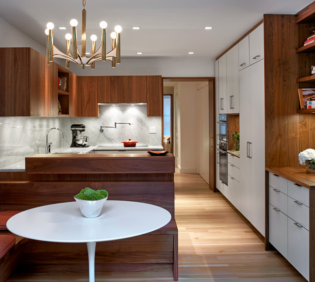 Inspiration for a 1950s u-shaped light wood floor eat-in kitchen remodel in New York with flat-panel cabinets, dark wood cabinets, gray backsplash and a peninsula