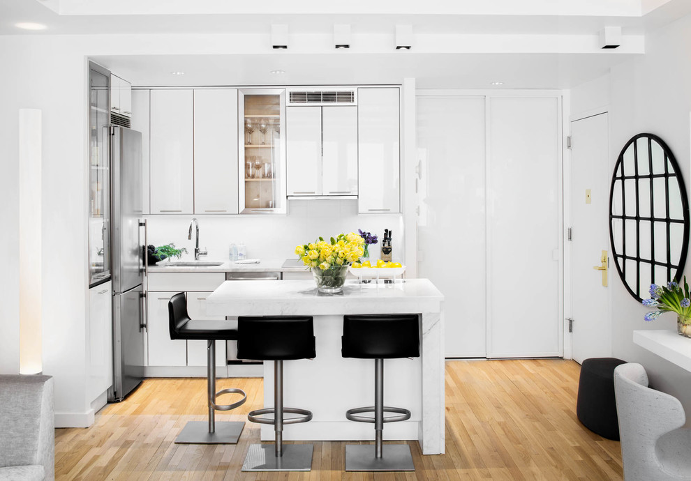 Example of a small trendy l-shaped light wood floor and brown floor open concept kitchen design in New York with an undermount sink, flat-panel cabinets, white cabinets, marble countertops, white backsplash, stainless steel appliances and an island