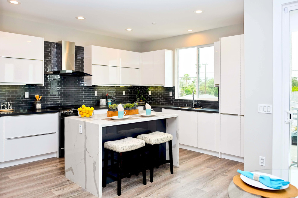 Example of a mid-sized trendy u-shaped light wood floor and brown floor eat-in kitchen design in Orange County with flat-panel cabinets, white cabinets, quartz countertops, black backsplash, ceramic backsplash, black appliances, an island, black countertops and a double-bowl sink
