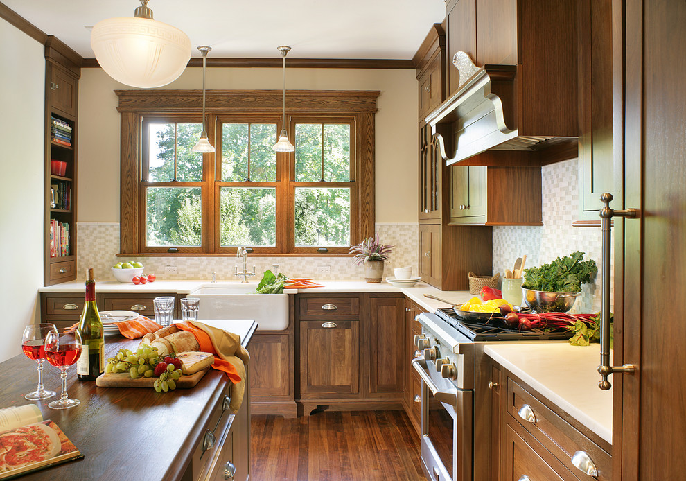 Arts and crafts kitchen photo in Huntington with wood countertops, a farmhouse sink, dark wood cabinets, beige backsplash, shaker cabinets and stainless steel appliances