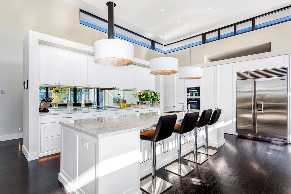 Contemporary galley kitchen in Sydney with a double-bowl sink, shaker cabinets, white cabinets, stainless steel appliances, dark hardwood floors and an island.