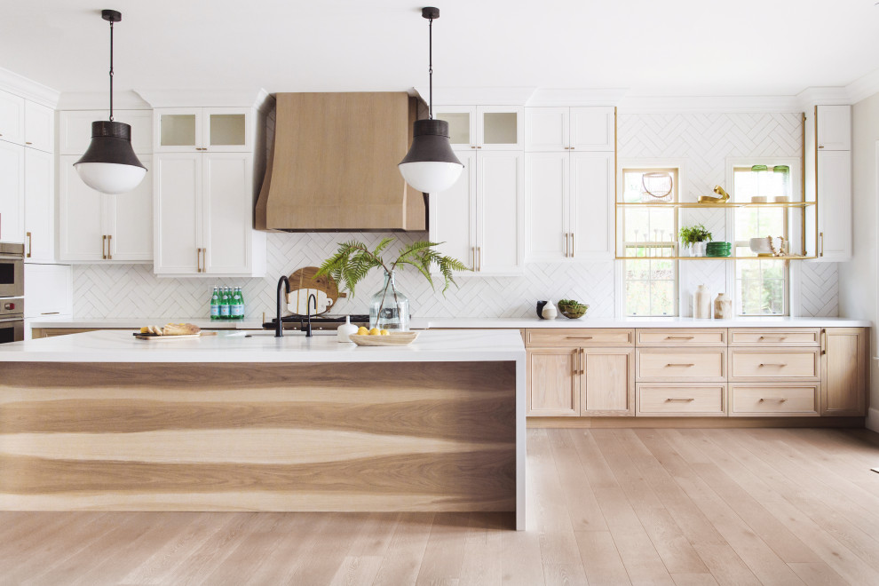 Transitional l-shaped medium tone wood floor and brown floor open concept kitchen photo in San Diego with an undermount sink, recessed-panel cabinets, light wood cabinets, white backsplash, stainless steel appliances, an island and white countertops
