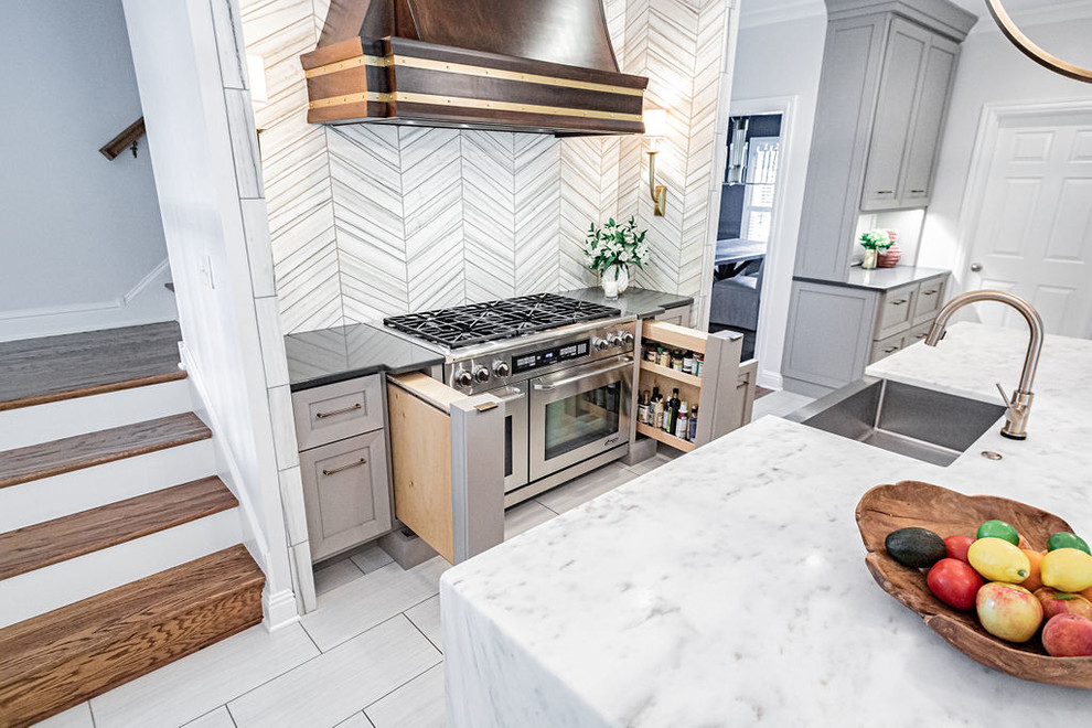 Inspiration for a large modern u-shaped porcelain tile and gray floor kitchen remodel in Other with a farmhouse sink, gray cabinets, marble countertops, gray backsplash, marble backsplash, stainless steel appliances, an island and multicolored countertops