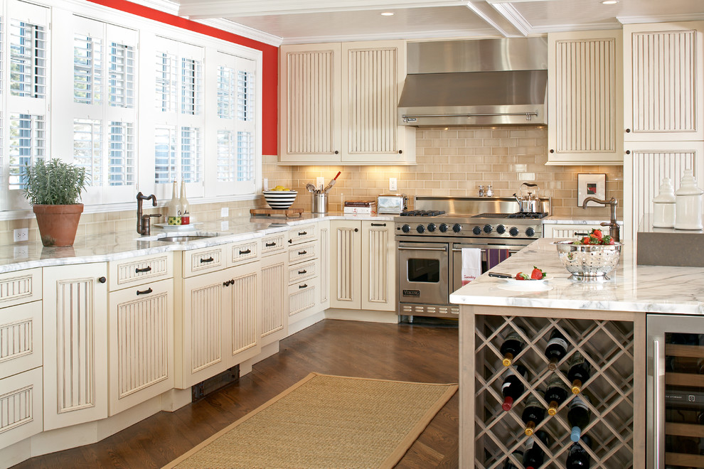 Design ideas for a large nautical l-shaped kitchen in Boston with stainless steel appliances, a submerged sink, distressed cabinets, marble worktops, beige splashback, ceramic splashback, medium hardwood flooring, an island and recessed-panel cabinets.