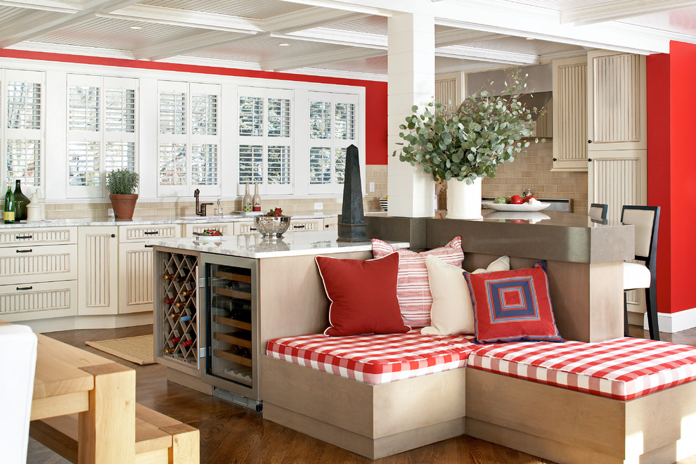 Example of a large beach style l-shaped medium tone wood floor eat-in kitchen design in Boston with recessed-panel cabinets, beige cabinets, beige backsplash, subway tile backsplash, marble countertops, an island, an undermount sink and stainless steel appliances