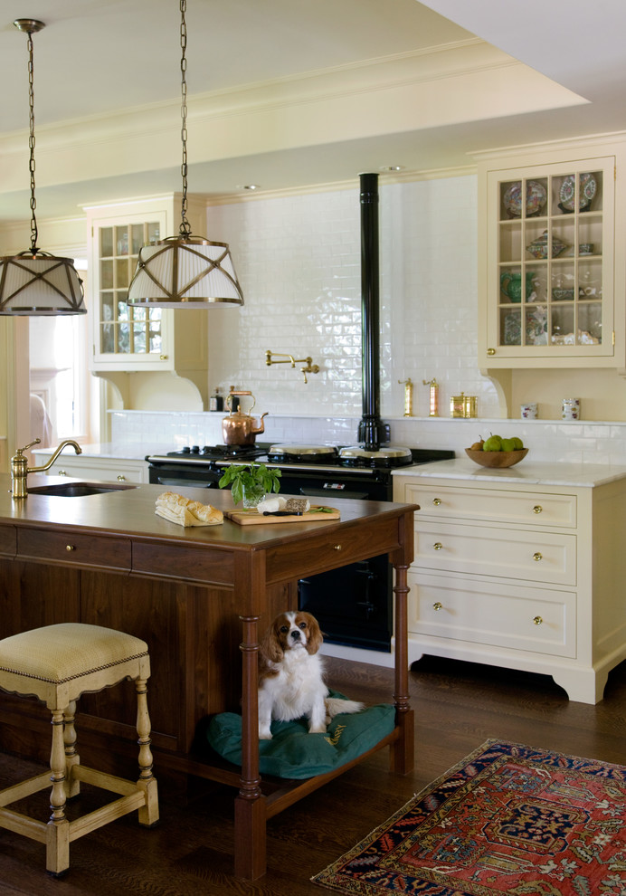 Ornate dark wood floor kitchen photo in Boston with yellow cabinets, marble countertops, white backsplash, subway tile backsplash, black appliances, an island, a single-bowl sink and glass-front cabinets