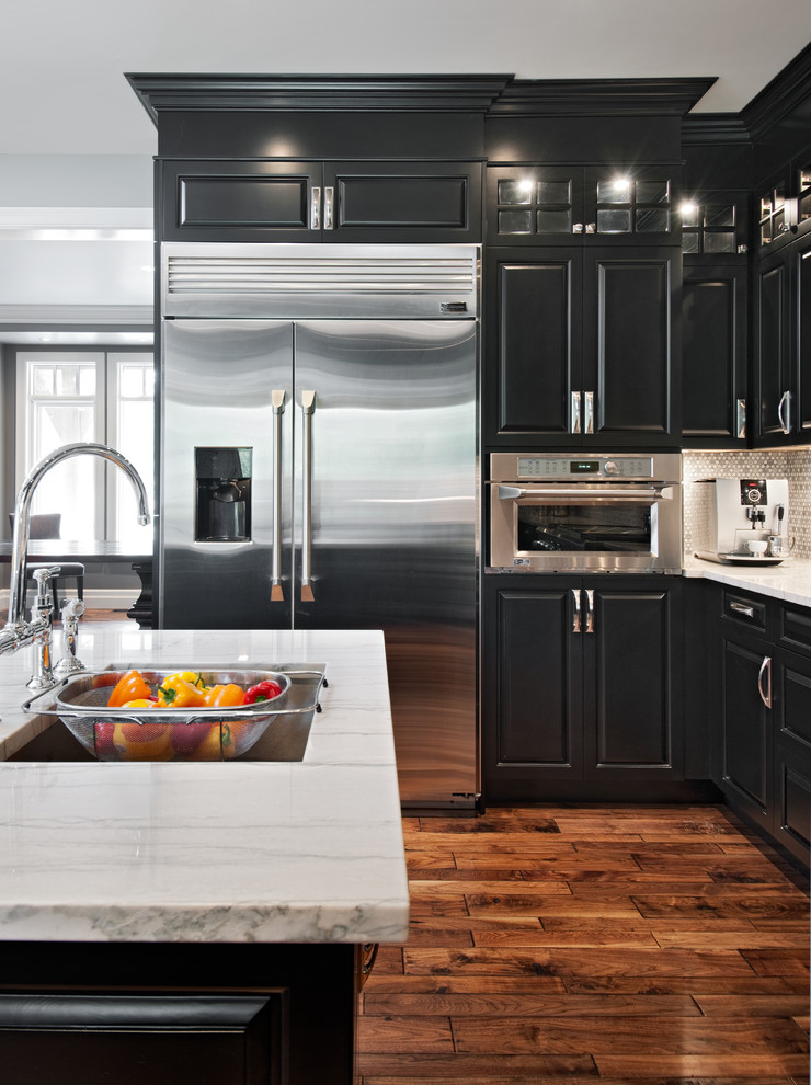 Inspiration for a timeless brown floor kitchen remodel in Ottawa with stainless steel appliances, a single-bowl sink, raised-panel cabinets, marble countertops, metallic backsplash and mosaic tile backsplash