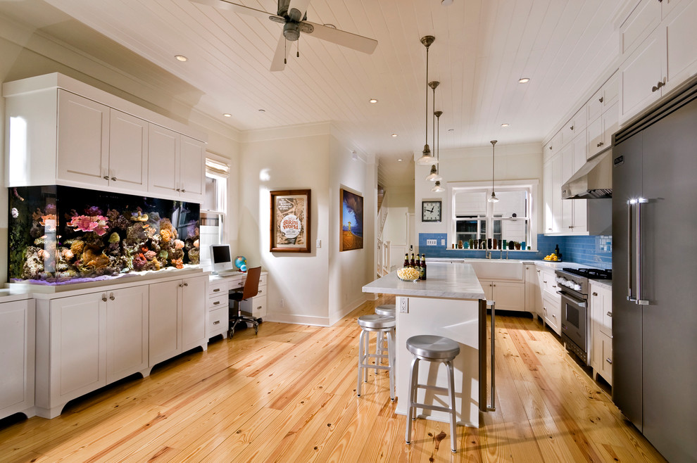 Inspiration for a tropical kitchen remodel in Orange County with a farmhouse sink, shaker cabinets, white cabinets, blue backsplash, subway tile backsplash and stainless steel appliances
