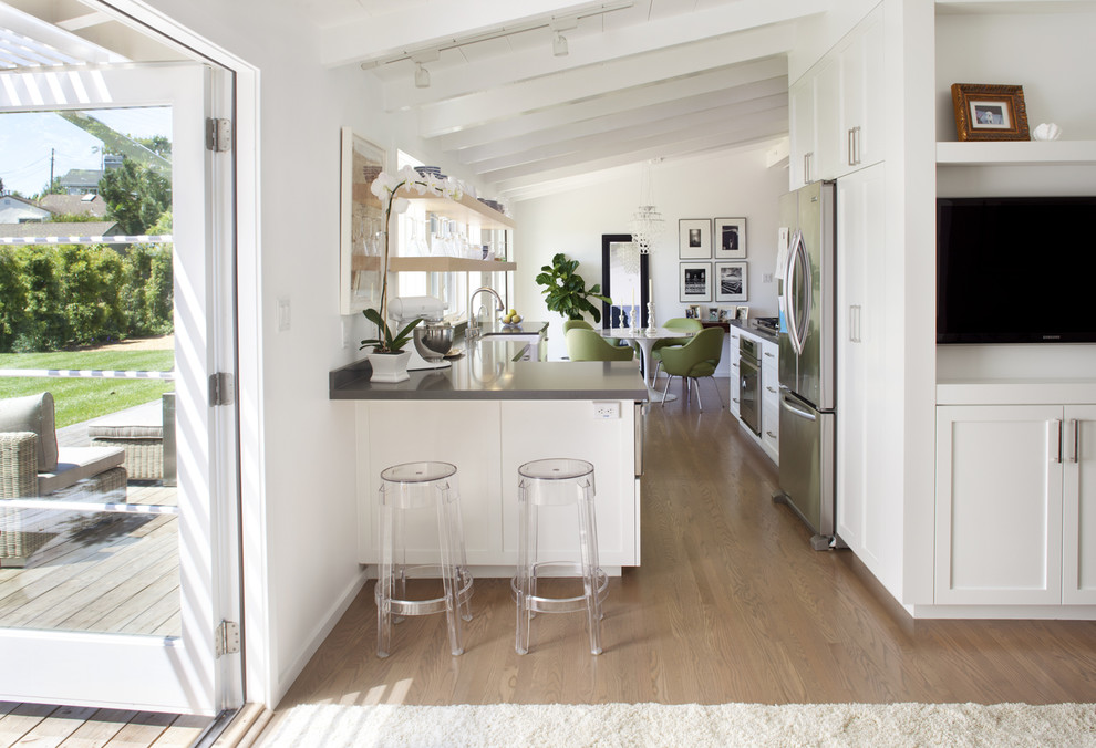 Trendy u-shaped kitchen photo in San Francisco with shaker cabinets, stainless steel appliances, white cabinets and a farmhouse sink