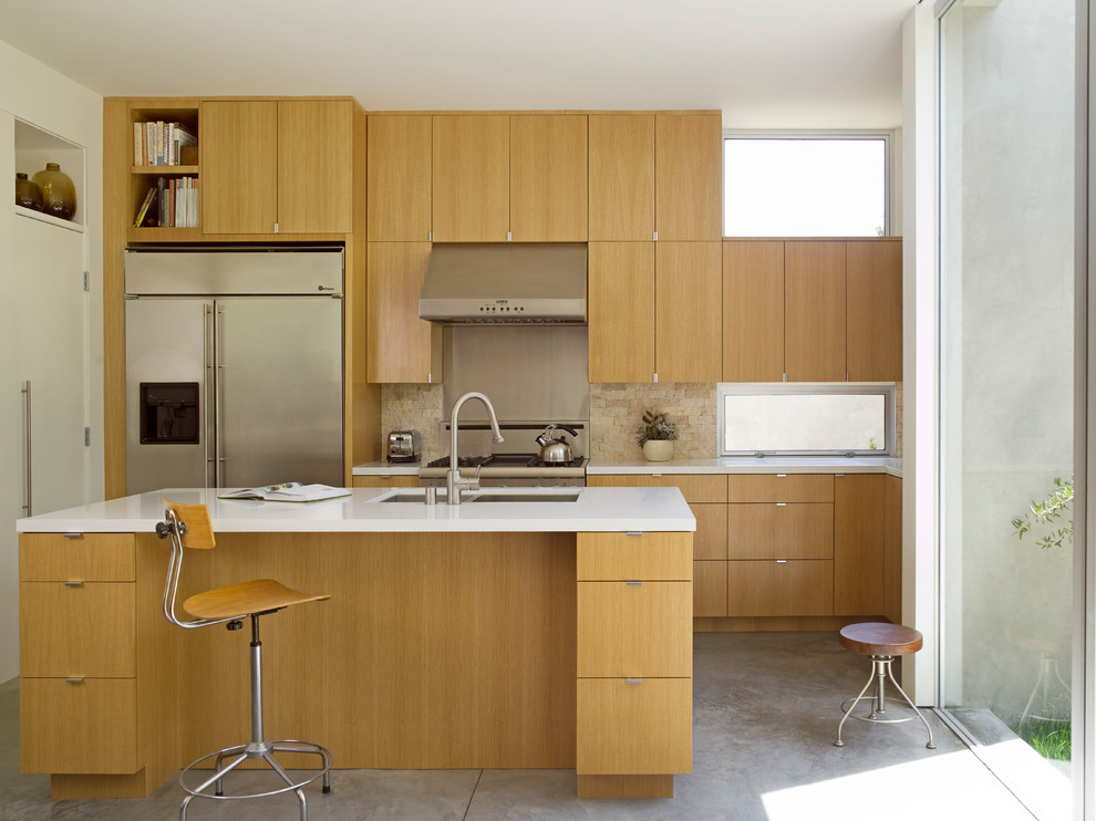 Inspiration for a mid-sized modern l-shaped concrete floor and gray floor open concept kitchen remodel in Los Angeles with an undermount sink, flat-panel cabinets, medium tone wood cabinets, quartz countertops, stone tile backsplash, stainless steel appliances, an island and beige backsplash