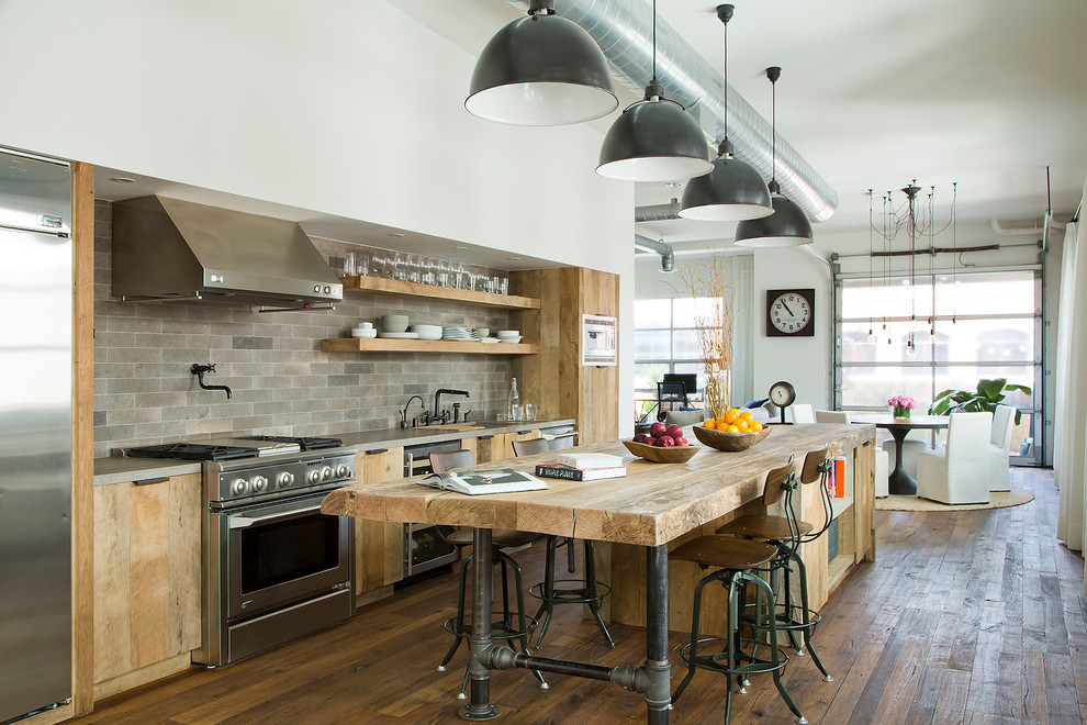 Large urban galley dark wood floor open concept kitchen photo in Los Angeles with flat-panel cabinets, an island, wood countertops, gray backsplash, stainless steel appliances and light wood cabinets