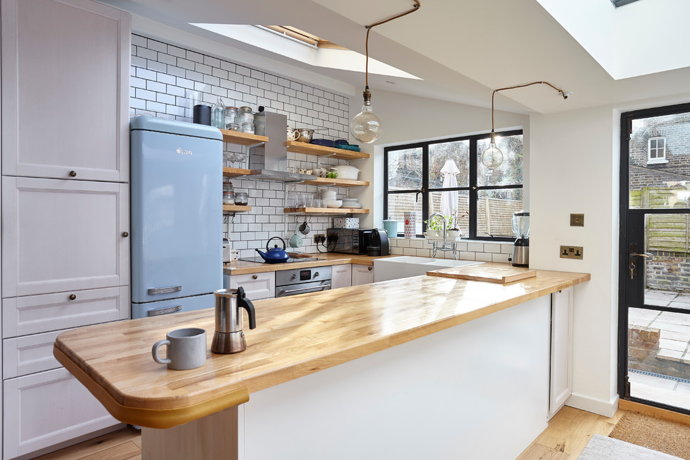 Example of a small country u-shaped light wood floor kitchen design in London with a farmhouse sink, recessed-panel cabinets, white cabinets, wood countertops, white backsplash, subway tile backsplash, colored appliances and a peninsula