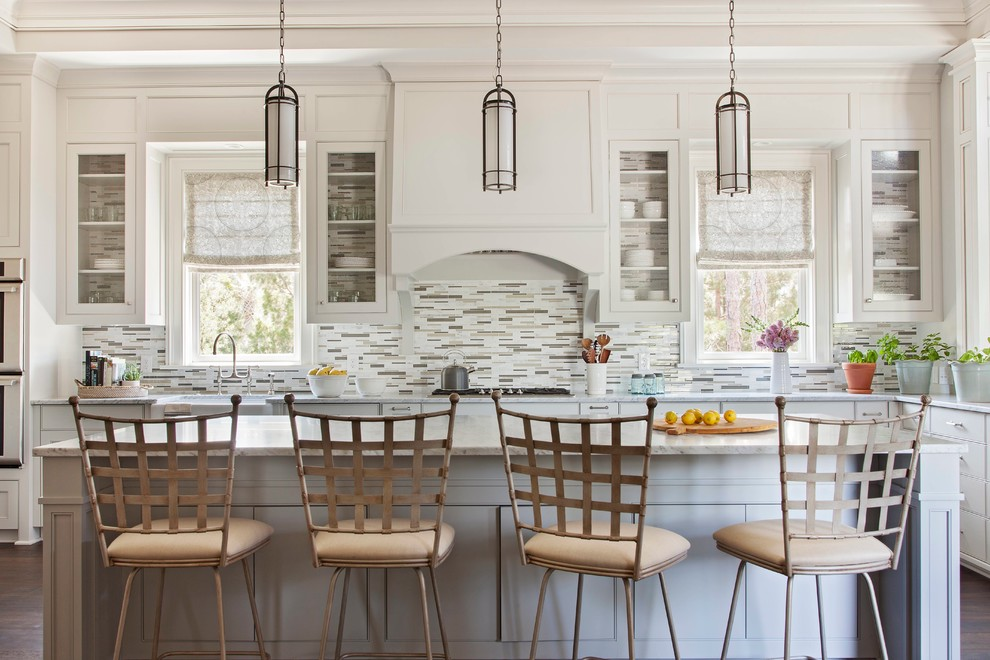 Photo of a large transitional u-shaped eat-in kitchen in Charleston with a farmhouse sink, glass-front cabinets, white cabinets, marble benchtops, white splashback, mosaic tile splashback, dark hardwood floors and an island.