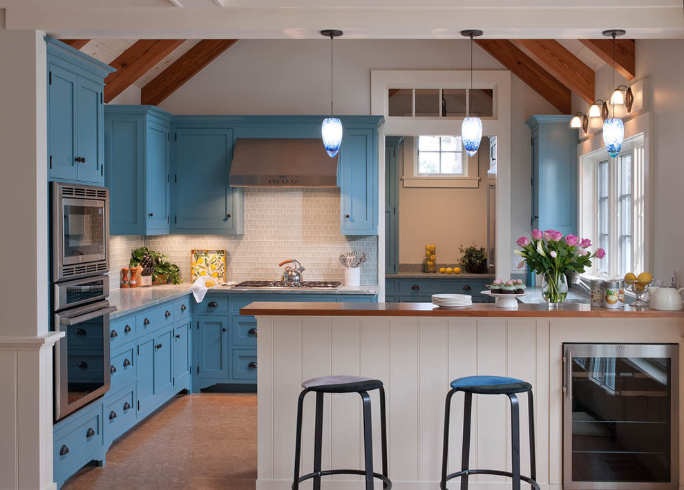 Example of a beach style cork floor kitchen design in Boston with shaker cabinets, blue cabinets, white backsplash, marble countertops, glass tile backsplash, an undermount sink and stainless steel appliances