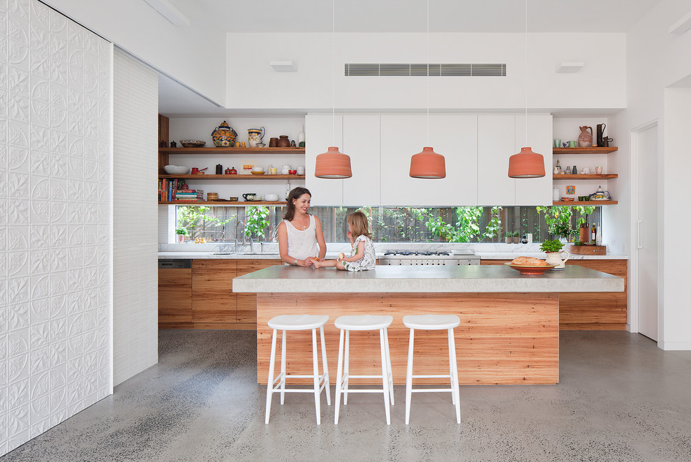 Inspiration for a mid-sized contemporary galley concrete floor kitchen remodel in Melbourne with an undermount sink, flat-panel cabinets, white cabinets, concrete countertops, glass sheet backsplash, stainless steel appliances and an island