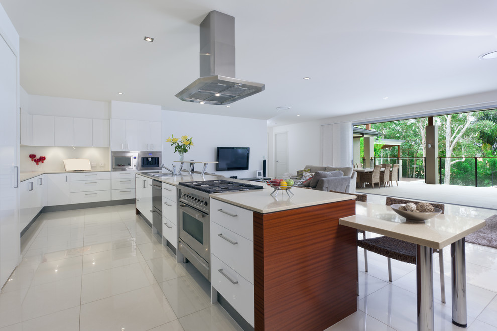 Example of a large minimalist l-shaped linoleum floor open concept kitchen design in Philadelphia with an undermount sink, flat-panel cabinets, white cabinets, white backsplash, stainless steel appliances and an island