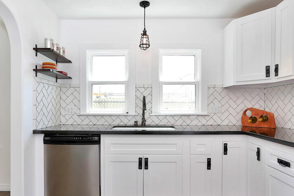 Modelo de cocina clásica renovada con fregadero bajoencimera, armarios estilo shaker, puertas de armario blancas, encimera de granito, salpicadero blanco, salpicadero de azulejos tipo metro y electrodomésticos de acero inoxidable