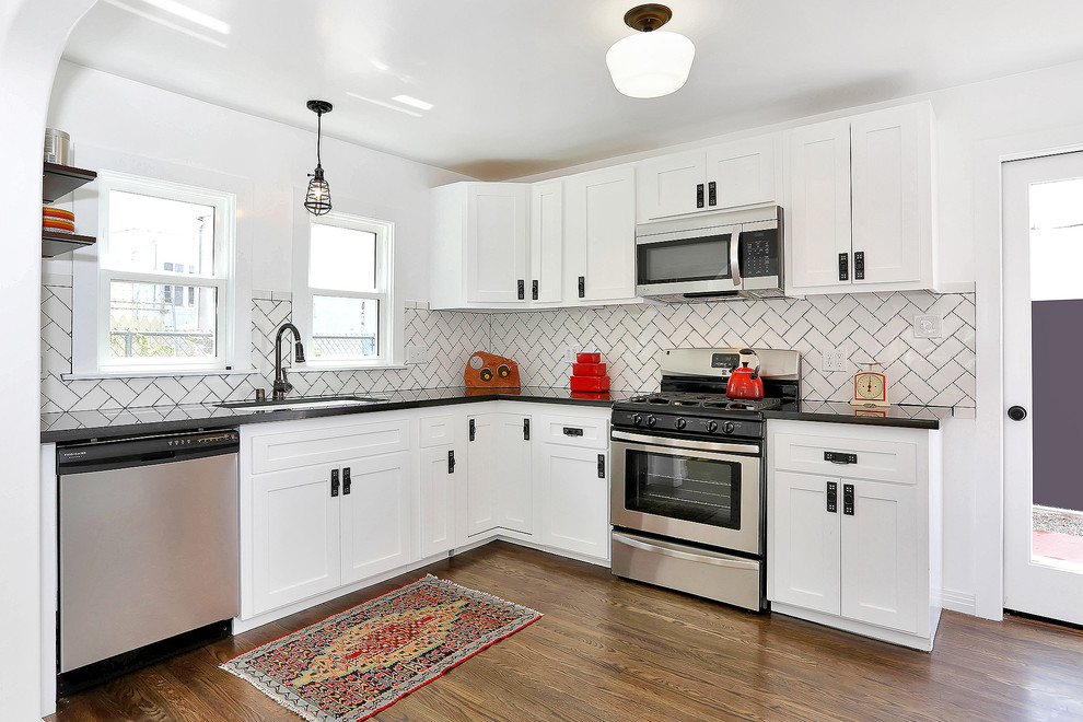 Transitional kitchen photo in Los Angeles with an undermount sink, shaker cabinets, white cabinets, granite countertops, white backsplash, subway tile backsplash and stainless steel appliances
