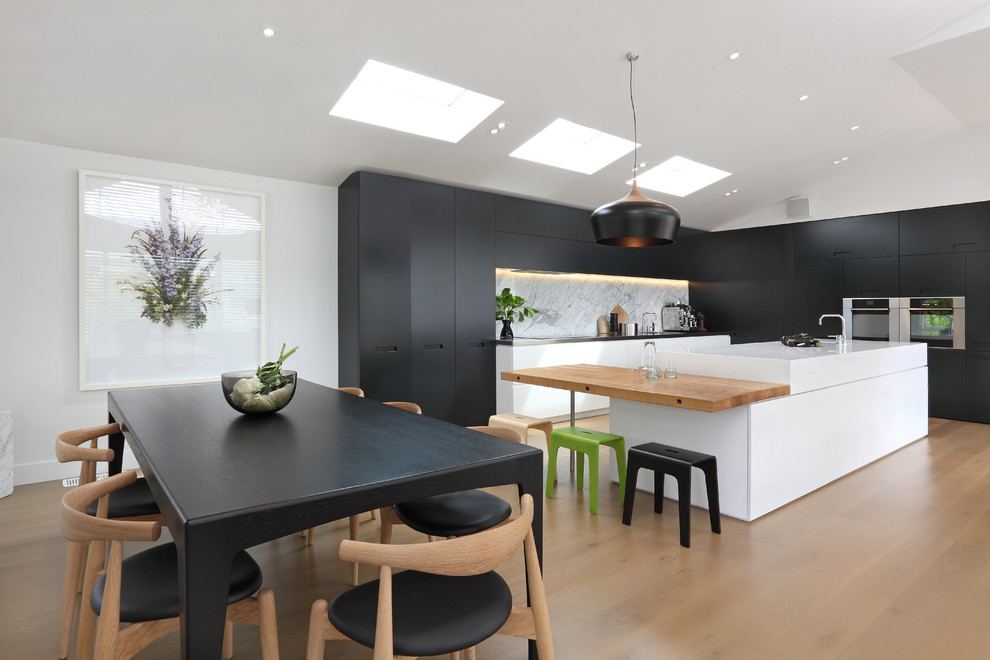 Inspiration for a contemporary eat-in kitchen remodel in Auckland with stainless steel appliances, wood countertops, flat-panel cabinets, white backsplash and stone slab backsplash
