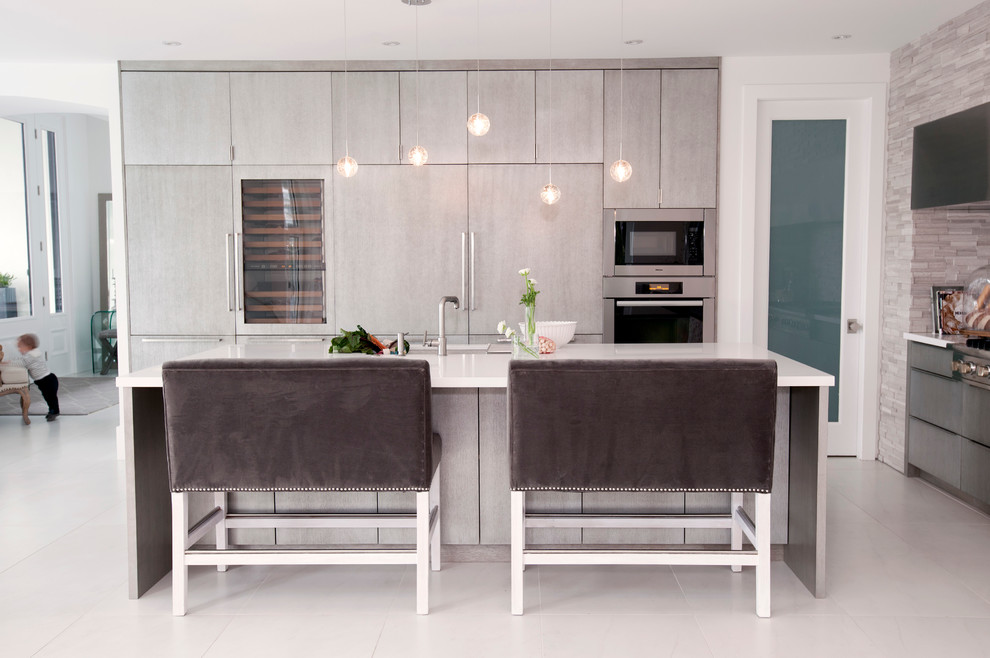 Kitchen - contemporary kitchen idea in Vancouver with flat-panel cabinets, gray cabinets, gray backsplash, stone tile backsplash and paneled appliances