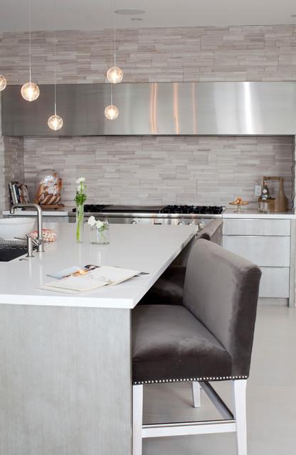 Foto de cocina contemporánea con armarios con paneles lisos, puertas de armario grises, salpicadero verde, salpicadero de azulejos de piedra y electrodomésticos de acero inoxidable