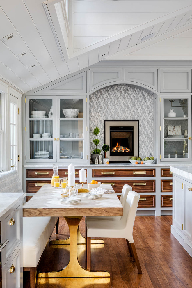 Example of a beach style medium tone wood floor and brown floor eat-in kitchen design in Providence with glass-front cabinets, gray cabinets, multicolored backsplash and white countertops