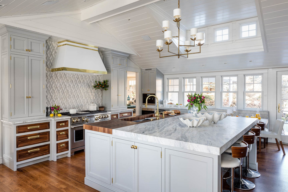 Beach style medium tone wood floor and brown floor eat-in kitchen photo in Providence with an undermount sink, recessed-panel cabinets, gray cabinets, multicolored backsplash, stainless steel appliances, an island and white countertops