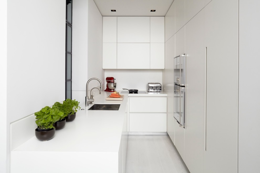 Photo of a modern l-shaped enclosed kitchen in London with a submerged sink, flat-panel cabinets, white cabinets, integrated appliances and white splashback.