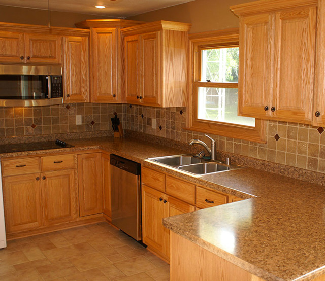 Inspiration for a large timeless u-shaped cement tile floor and beige floor eat-in kitchen remodel in Milwaukee with a double-bowl sink, raised-panel cabinets, medium tone wood cabinets, granite countertops, beige backsplash, stone tile backsplash, stainless steel appliances and a peninsula