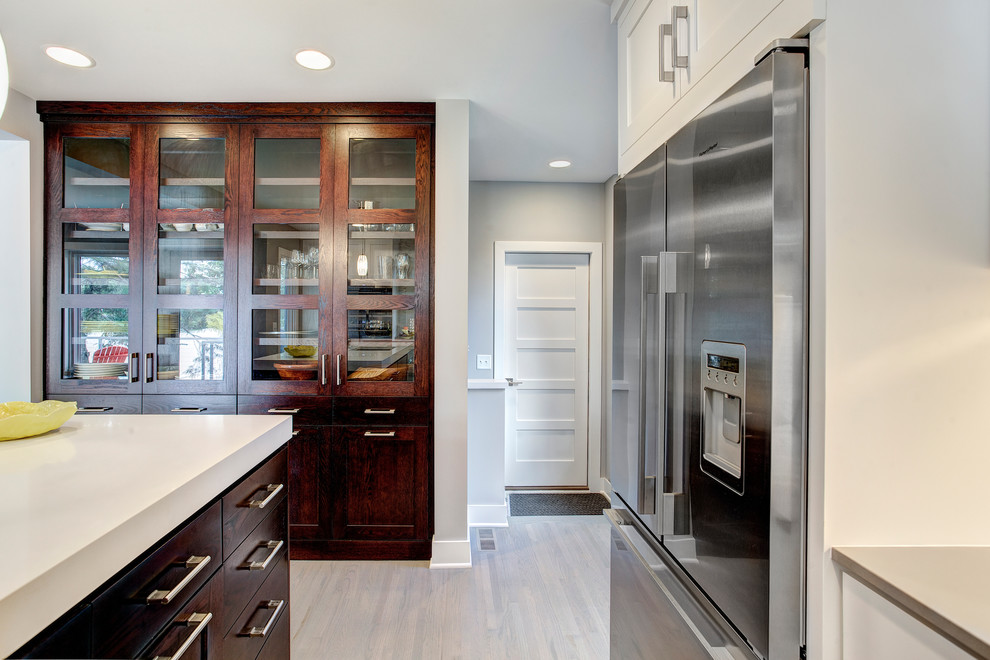 Photo of a medium sized contemporary l-shaped kitchen/diner in Minneapolis with a submerged sink, white cabinets, quartz worktops, white splashback, glass tiled splashback, stainless steel appliances, medium hardwood flooring and an island.