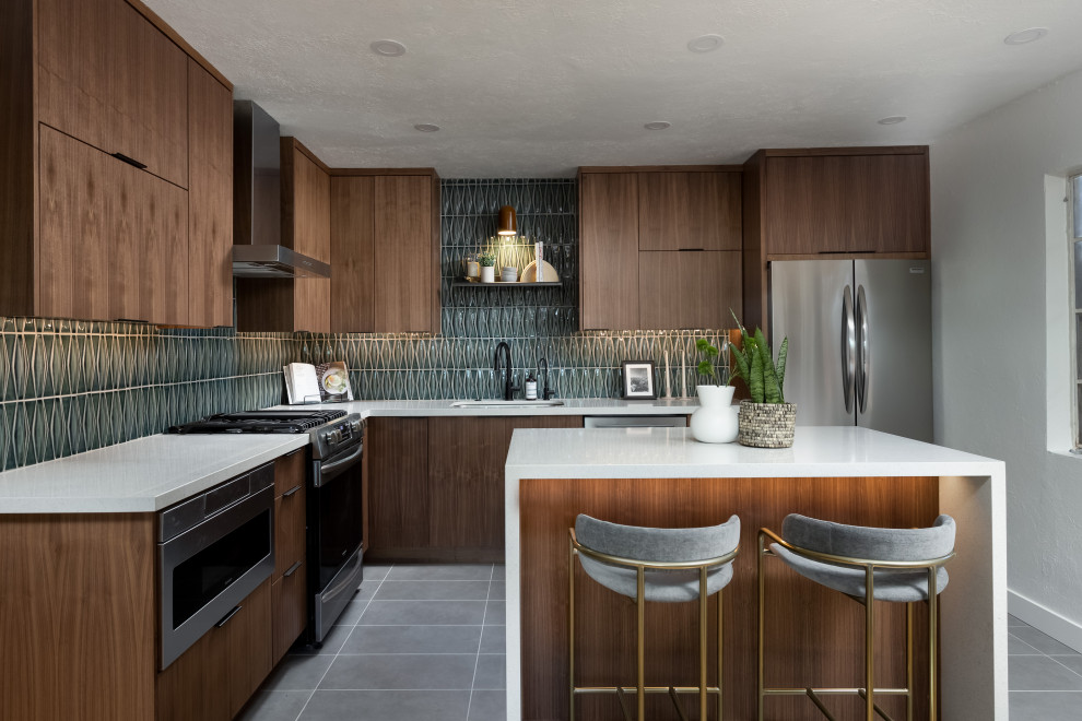 Inspiration for a mid-sized contemporary l-shaped porcelain tile and gray floor enclosed kitchen remodel in Phoenix with an undermount sink, flat-panel cabinets, medium tone wood cabinets, quartz countertops, green backsplash, ceramic backsplash, stainless steel appliances, an island and white countertops