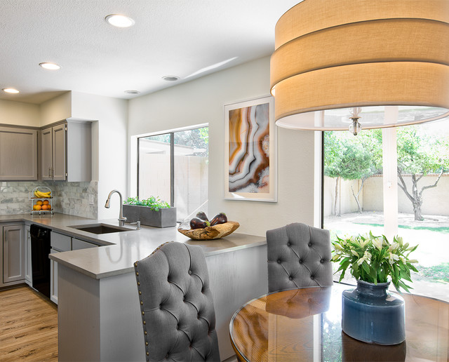 Eat-in kitchen - small contemporary galley eat-in kitchen idea in Phoenix with an undermount sink, raised-panel cabinets, gray cabinets, quartz countertops, gray backsplash, stone tile backsplash and black appliances