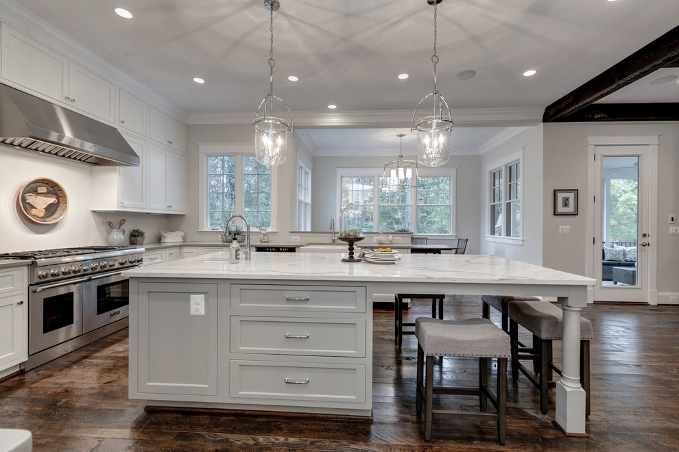 Example of a large cottage u-shaped dark wood floor open concept kitchen design in DC Metro with a farmhouse sink, shaker cabinets, white cabinets, quartzite countertops, white backsplash, stainless steel appliances and an island