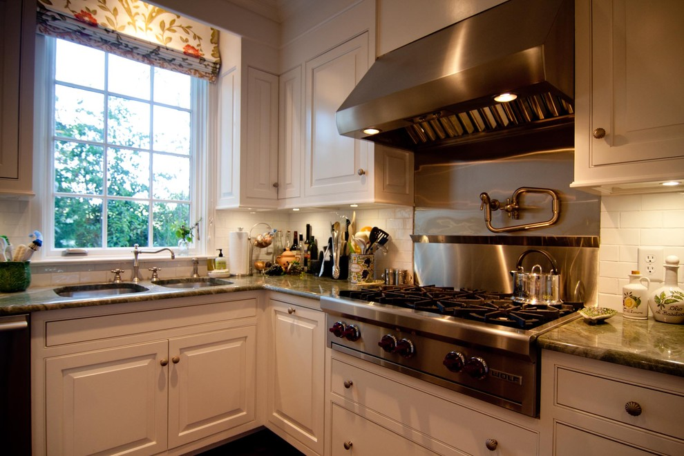 Example of a large classic kitchen design in Atlanta with an undermount sink, white cabinets, granite countertops, white backsplash, ceramic backsplash and stainless steel appliances