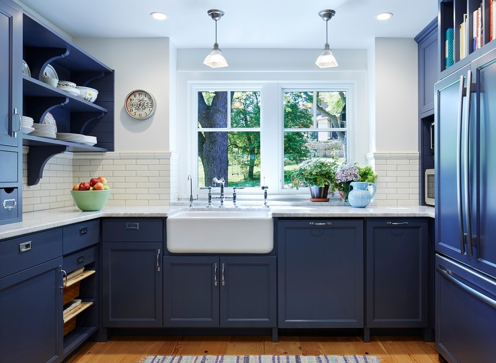 Inspiration for a large timeless u-shaped medium tone wood floor kitchen remodel in Minneapolis with a farmhouse sink, recessed-panel cabinets, blue cabinets, marble countertops, white backsplash, stainless steel appliances and an island