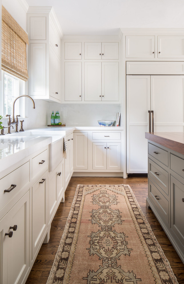 Cottage l-shaped medium tone wood floor kitchen photo in Boston with a farmhouse sink, shaker cabinets, white cabinets, paneled appliances and an island