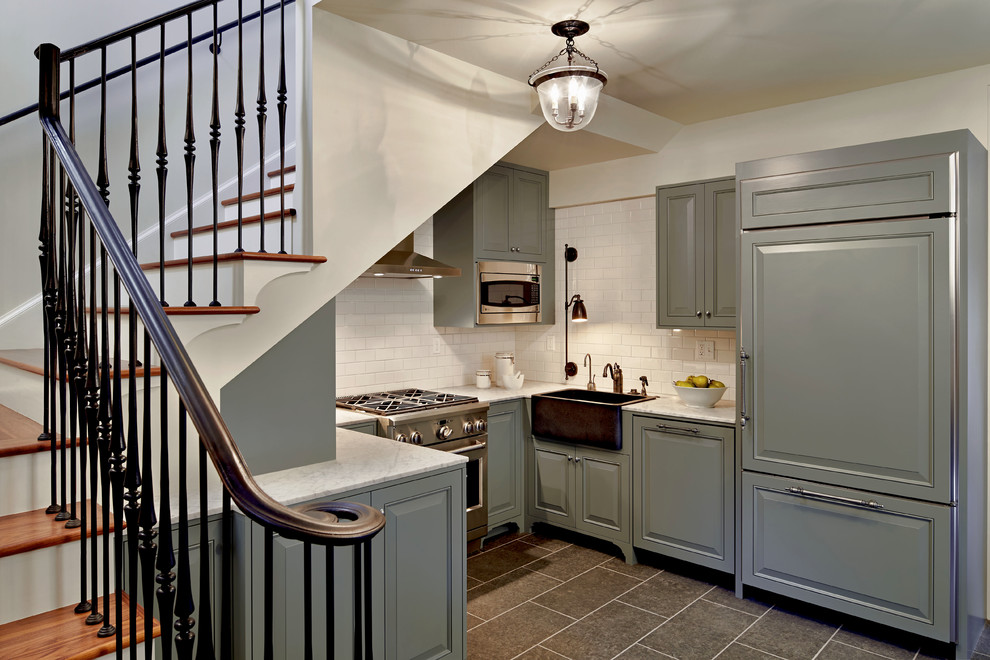 Inspiration for a timeless u-shaped kitchen remodel in Seattle with a farmhouse sink, raised-panel cabinets, blue cabinets, white backsplash, subway tile backsplash, paneled appliances and marble countertops