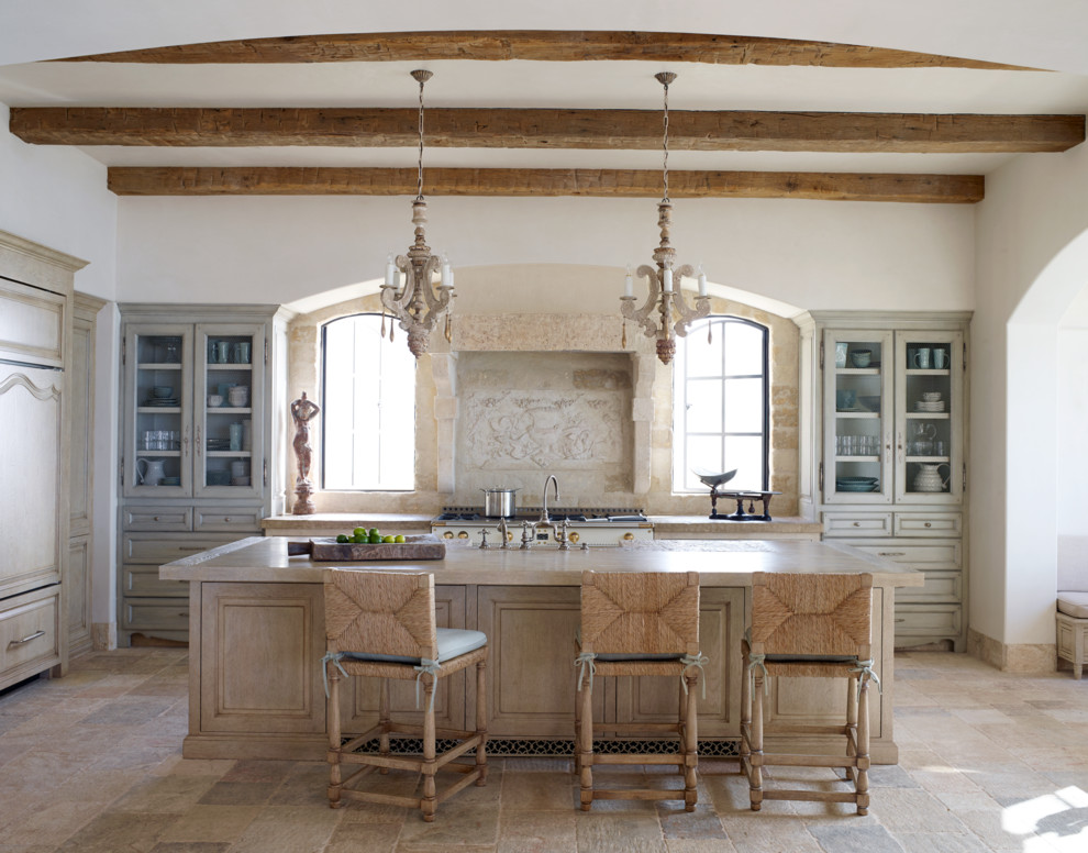 Mid-sized tuscan l-shaped limestone floor and beige floor eat-in kitchen photo in Orange County with glass-front cabinets, beige cabinets, beige backsplash, paneled appliances, an island, a farmhouse sink, quartzite countertops and limestone backsplash