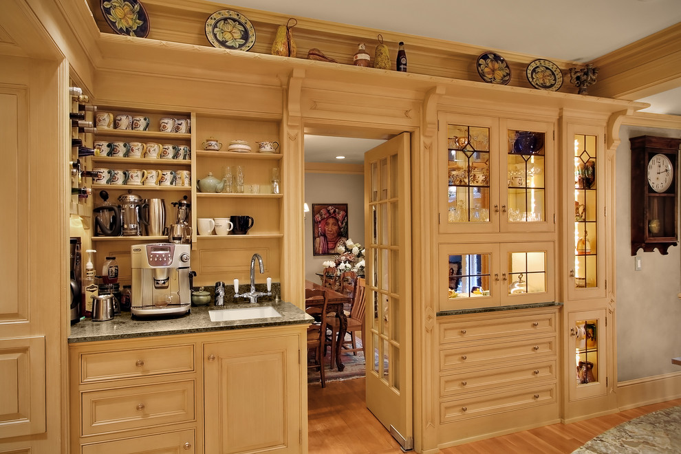 Example of a classic enclosed kitchen design in Seattle with glass-front cabinets and beige cabinets