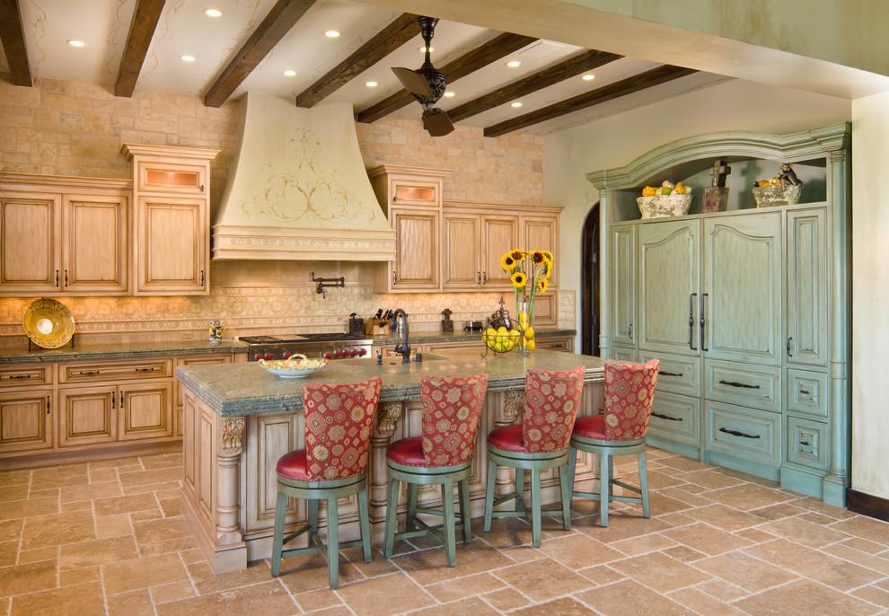 Inspiration for a mediterranean kitchen remodel in Orange County with raised-panel cabinets, light wood cabinets, granite countertops, beige backsplash, stone tile backsplash and paneled appliances