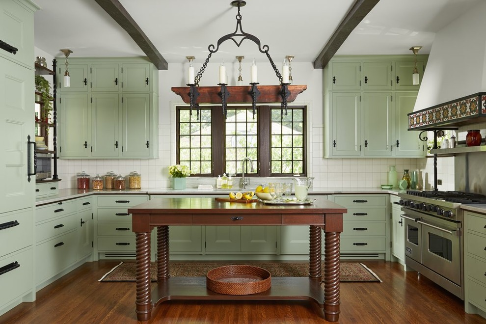 Example of a tuscan u-shaped medium tone wood floor and brown floor kitchen design in Minneapolis with an undermount sink, recessed-panel cabinets, green cabinets, white backsplash, stainless steel appliances, an island and white countertops