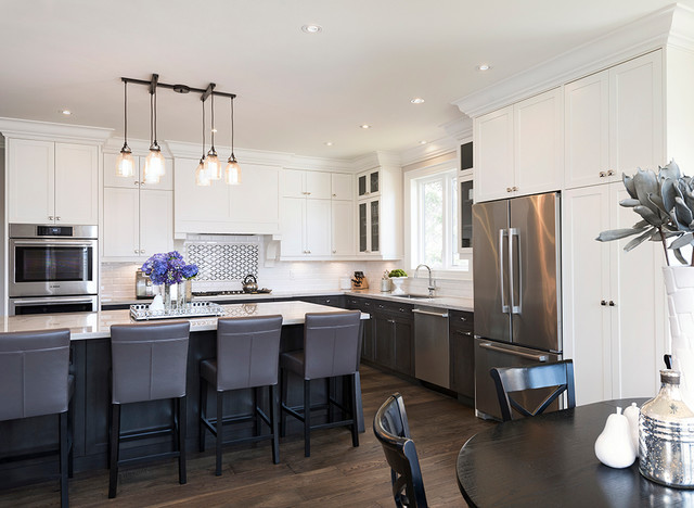 Large transitional l-shaped dark wood floor open concept kitchen photo in Toronto with an undermount sink, recessed-panel cabinets, white cabinets, quartzite countertops, white backsplash, subway tile backsplash, stainless steel appliances and an island
