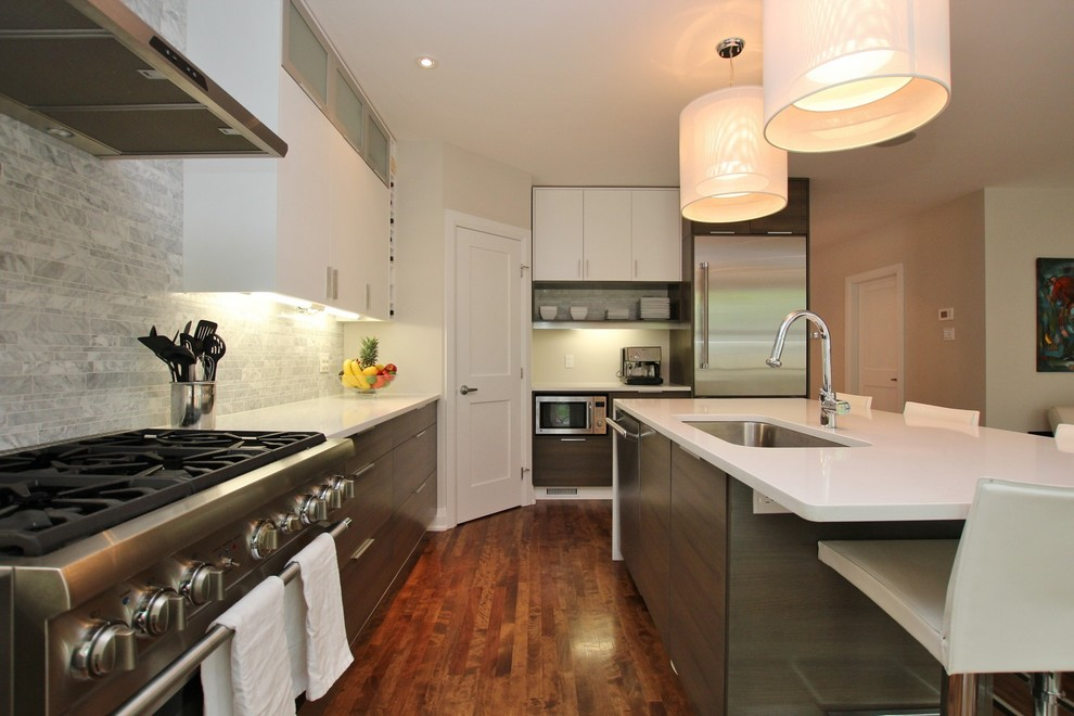 Inspiration for a mid-sized contemporary u-shaped medium tone wood floor and brown floor eat-in kitchen remodel in Ottawa with an undermount sink, flat-panel cabinets, gray cabinets, gray backsplash, ceramic backsplash, stainless steel appliances, an island, quartz countertops and white countertops