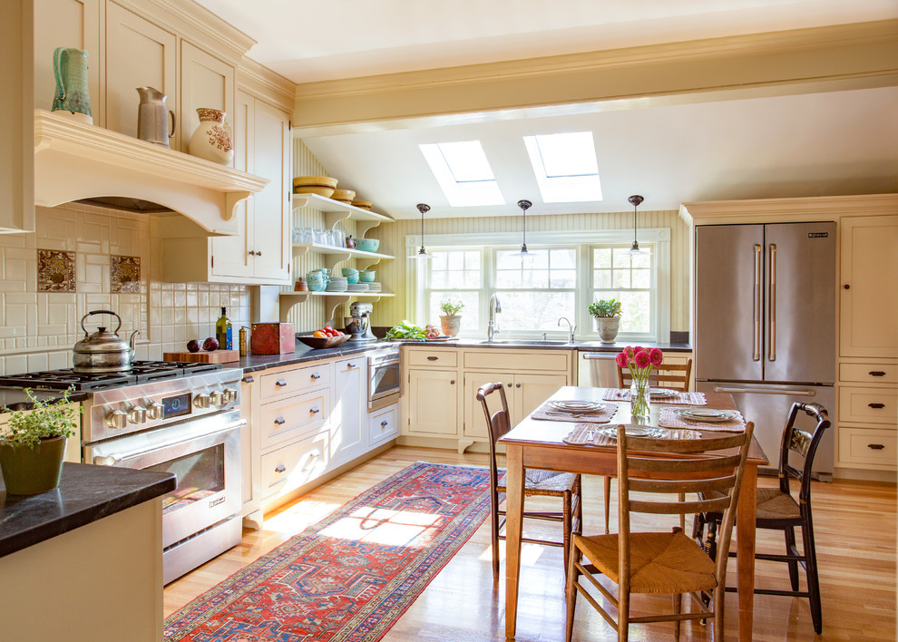 Inspiration for a mid-sized cottage u-shaped medium tone wood floor eat-in kitchen remodel in Boston with an undermount sink, beaded inset cabinets, soapstone countertops, white backsplash, ceramic backsplash, stainless steel appliances, no island and beige cabinets