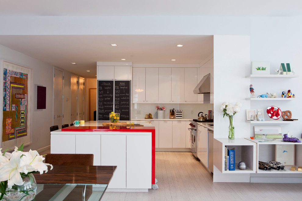 Mid-sized danish l-shaped light wood floor open concept kitchen photo in New York with an undermount sink, flat-panel cabinets, white cabinets, solid surface countertops, white backsplash, glass sheet backsplash, stainless steel appliances, an island and red countertops