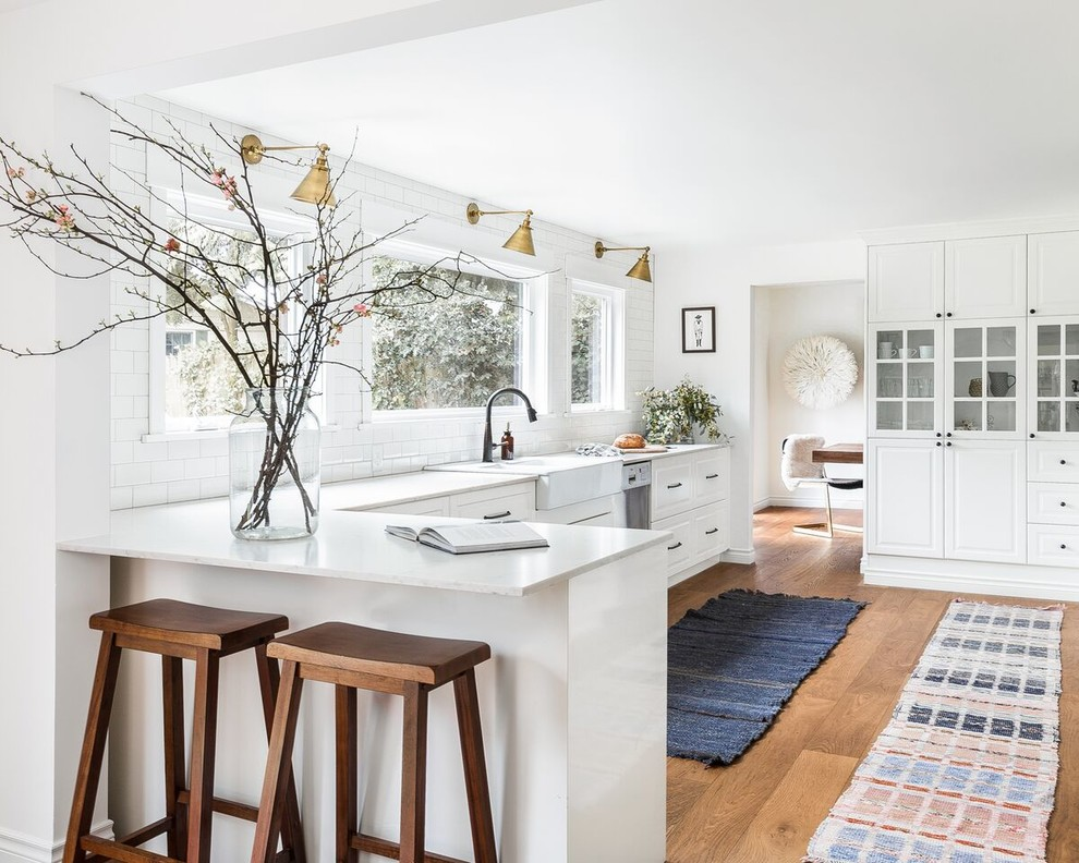 Example of a large country l-shaped medium tone wood floor and brown floor enclosed kitchen design in Seattle with a farmhouse sink, raised-panel cabinets, white cabinets, white backsplash, subway tile backsplash, stainless steel appliances, a peninsula and quartzite countertops