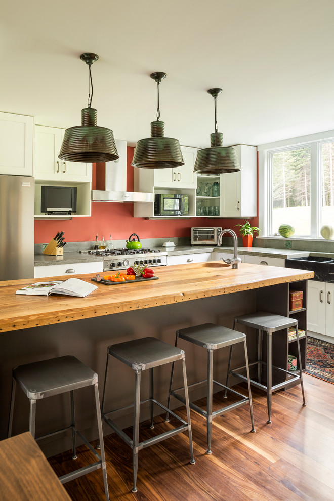 Kitchen - contemporary kitchen idea in Portland Maine with shaker cabinets, white cabinets, wood countertops, a farmhouse sink and stainless steel appliances