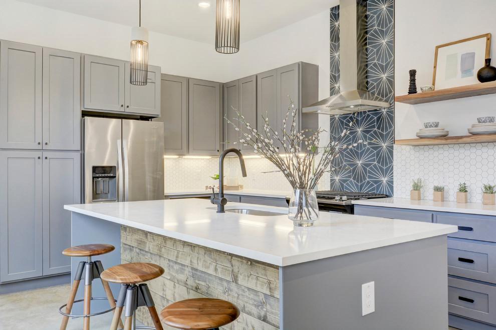 Diseño de cocinas en U clásico renovado, cerrado, con fregadero bajoencimera, armarios estilo shaker, puertas de armario grises, salpicadero blanco, electrodomésticos de acero inoxidable, una isla y suelo beige