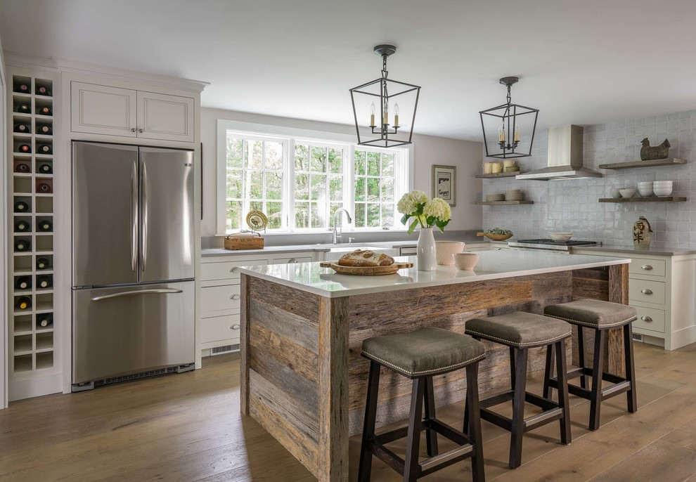 Kitchen - mid-sized farmhouse l-shaped light wood floor and brown floor kitchen idea in Boston with a farmhouse sink, recessed-panel cabinets, white cabinets, quartzite countertops, gray backsplash, porcelain backsplash, stainless steel appliances and an island